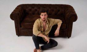 Alex wall sentado delante de un sofá